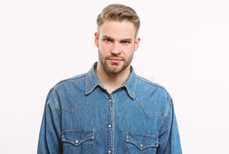 Το Hipster στο πουκάμισο τζιν φαίνεται ελκυστικό άσπρο υπόβαθρο Το άτομο εκαλλώπισε καλά τη γενειάδα και το βέβαιο πρόσωπο Καλά κ στοκ εικόνες