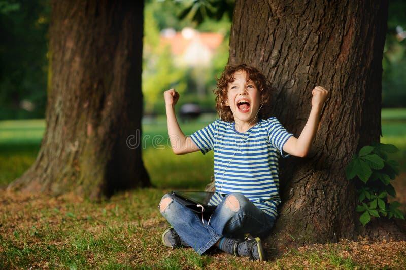 Το indignant αγόρι κάθεται κάτω από ένα δέντρο με την ταμπλέτα στην περιτύλιξη στοκ εικόνες
