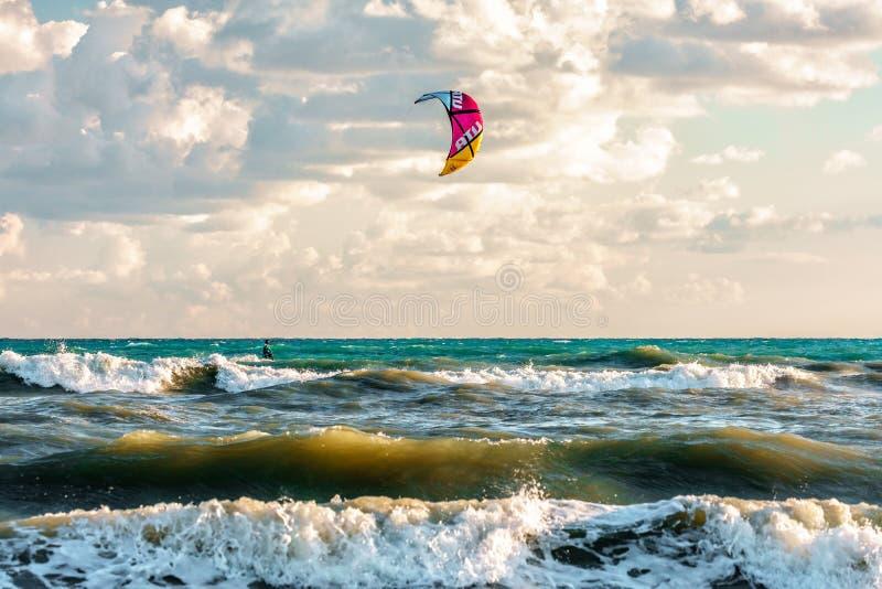 Το Kitesurfer οδηγά τον ικτίνο μέσω των κυμάτων σερφ του θυελλώδους σπασίματος Μαύρης Θάλασσας στην αμμώδη ακτή στοκ εικόνα