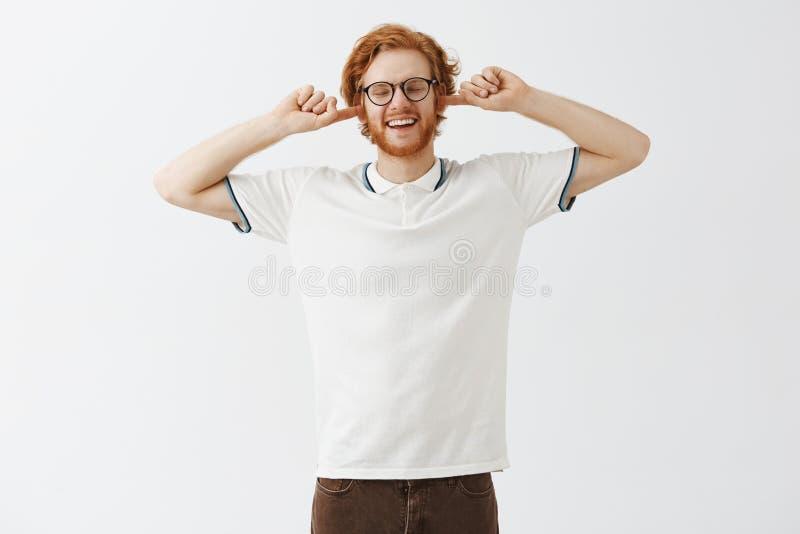 Το Lalala δεν μπορεί να σας ακούσει Παιδαριώδης και ξένοιαστος ευτυχής νέος redhead τύπος με τη γενειάδα στα γυαλιά και το άσπρο  στοκ εικόνες