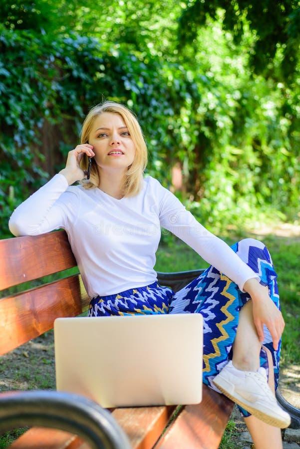 Το lap-top γυναικών στο πάρκο απολαμβάνει την πράσινους φύση και το καθαρό αέρα Το κορίτσι ονειροπόλο εκμεταλλεύεται on-line να ψ στοκ φωτογραφίες
