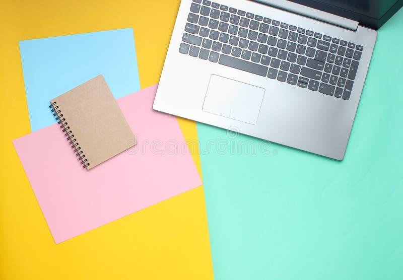 Το lap-top, σημειωματάριο σε ένα χρωματισμένο υπόβαθρο κρητιδογραφιών, σύγχρονος χώρος εργασίας, μινιμαλισμός, επίπεδο βάζει το ύ στοκ εικόνα