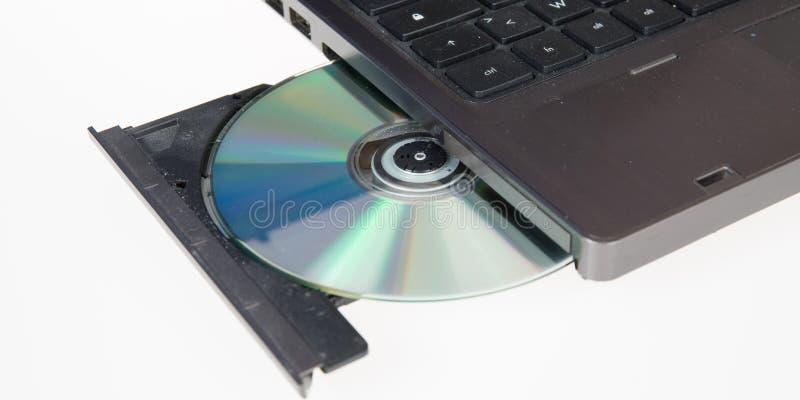 το lap-top φορτώνεται με έναν ανοικτό δίσκο CD-$l*rom κίνησης DVD σε ένα λευκό στοκ εικόνα με δικαίωμα ελεύθερης χρήσης
