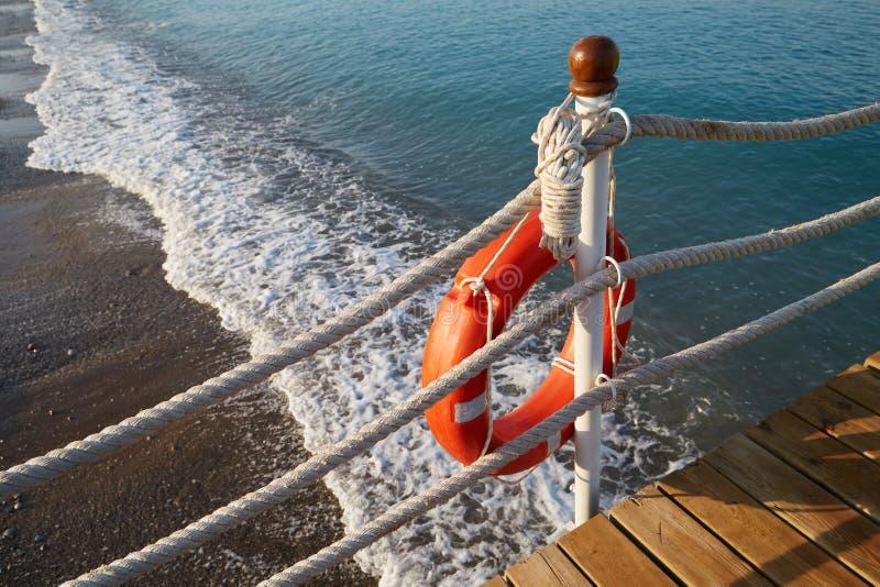 Το Lifebuoy με ένα σχοινί είναι στην άκρη του νερού στην παραλία στοκ φωτογραφίες