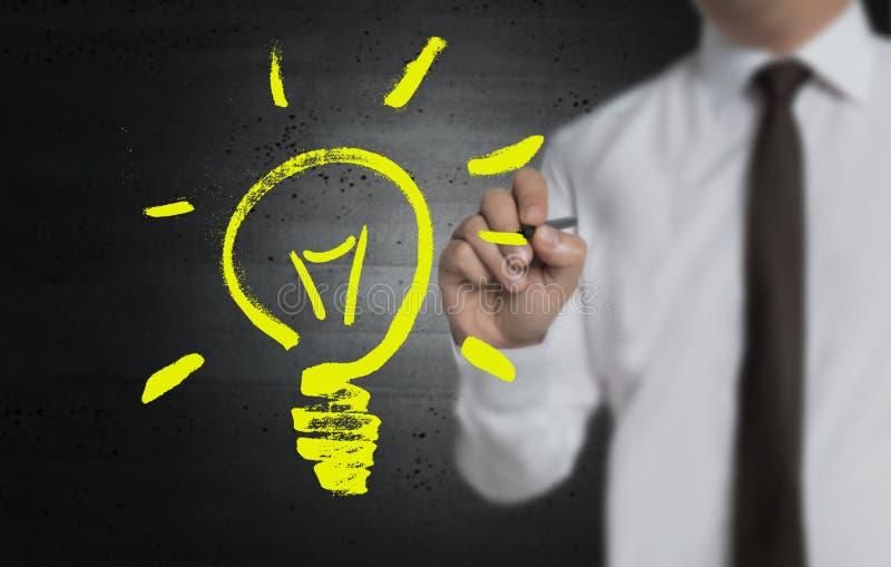 Το Lightbulb χρωματίζεται από τον επιχειρηματία στην οθόνη στοκ εικόνα με δικαίωμα ελεύθερης χρήσης