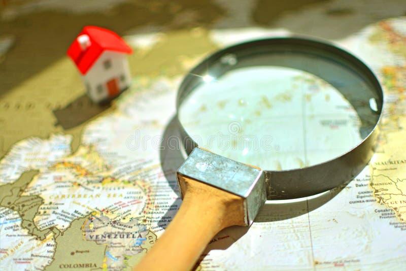 Το Loupe με μια ξύλινη λαβή και ένα μικροσκοπικό σπίτι βρίσκεται σε έναν παγκόσμιο χάρτη στοκ φωτογραφίες με δικαίωμα ελεύθερης χρήσης