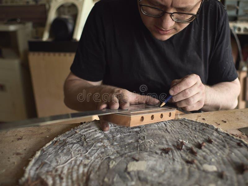 Το Luthier τροποποιεί το κεφάλι της κλασσικής κιθάρας στοκ εικόνες