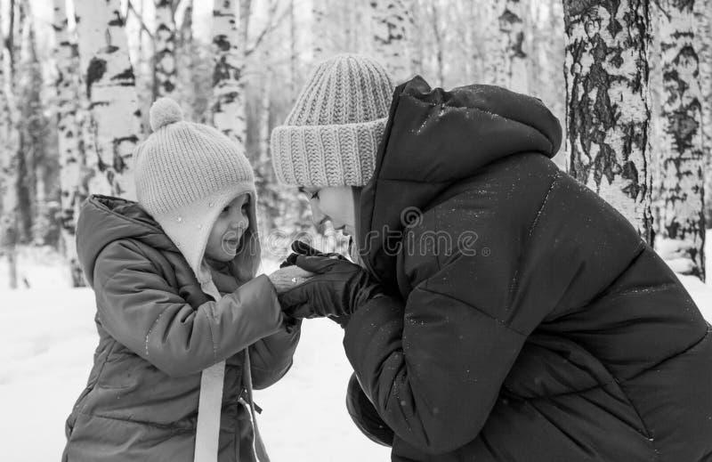 Το Mom δίνει την κόρη της θερμή στη χειμερινή δασική γραπτή φωτογραφία στοκ εικόνα με δικαίωμα ελεύθερης χρήσης