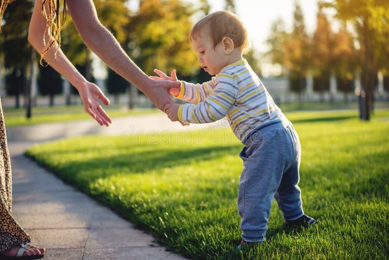 Το Mom βοηθά το χαριτωμένο περπάτημα μωρών σε έναν πράσινο χορτοτάπητα στη φύση μια ηλιόλουστη ημέρα φθινοπώρου Βήματα παιδιών έν στοκ εικόνα με δικαίωμα ελεύθερης χρήσης