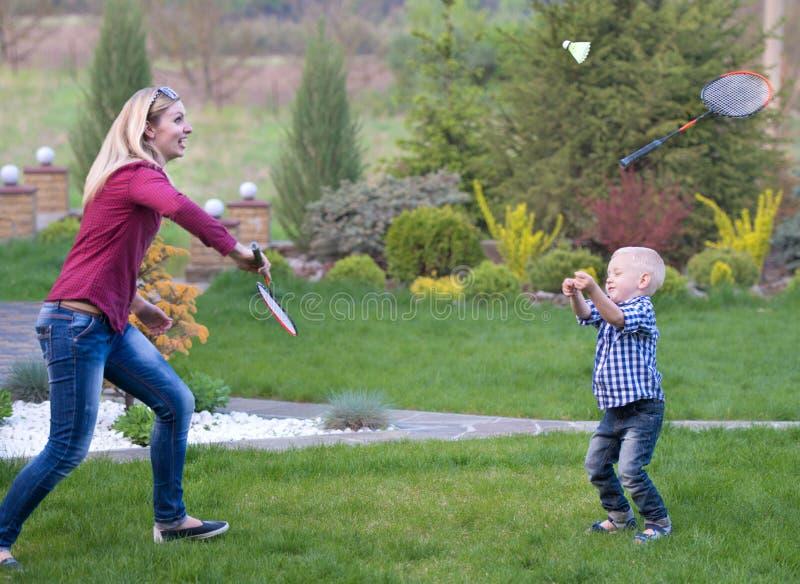 Το Mom διδάσκει το νέο γιο για να παίξει το μπάντμιντον Ενεργές οικογενειακές διακοπές στοκ φωτογραφία με δικαίωμα ελεύθερης χρήσης