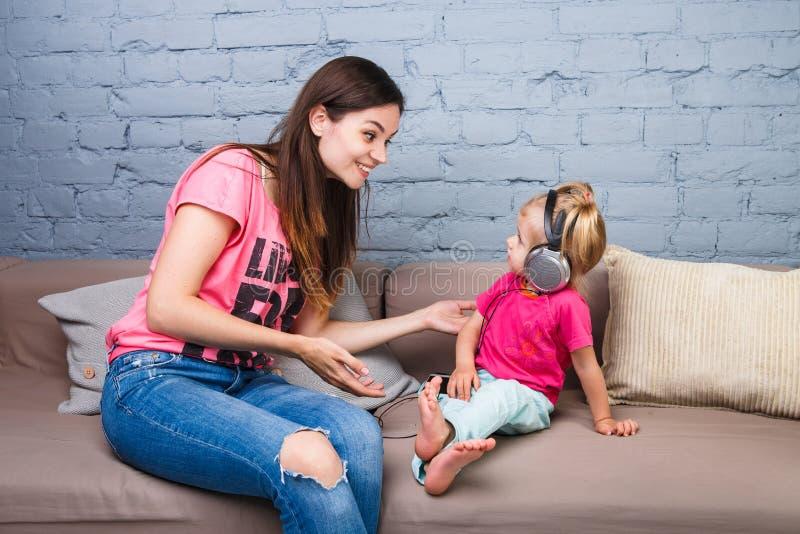 Το Mom και η κόρη ακούνε τη μουσική στα μεγάλα ακουστικά που τίθεται στο κεφάλι τους, καθμένος στον καναπέ Κρατά το τηλέφωνο στοκ εικόνες