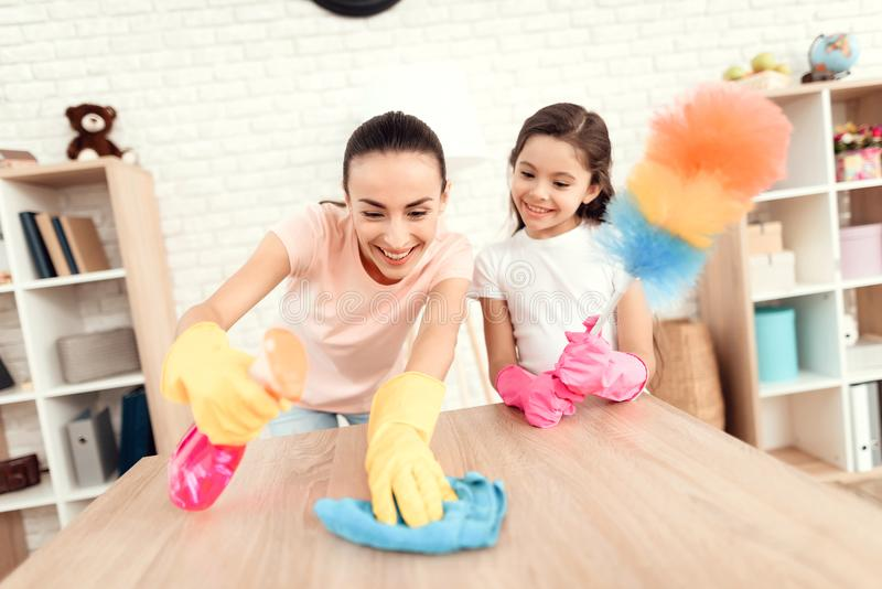 Το Mom και η κόρη καθαρίζουν στο σπίτι Σκουπίστε τα ράφια και τον πίνακα στοκ φωτογραφία