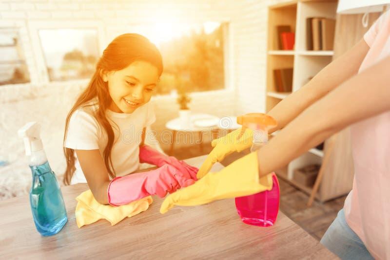 Το Mom και η κόρη καθαρίζουν στο σπίτι Στέκονται δίπλα στο να δειπνήσουν πίνακα και τον ανόητο γύρω στοκ φωτογραφίες
