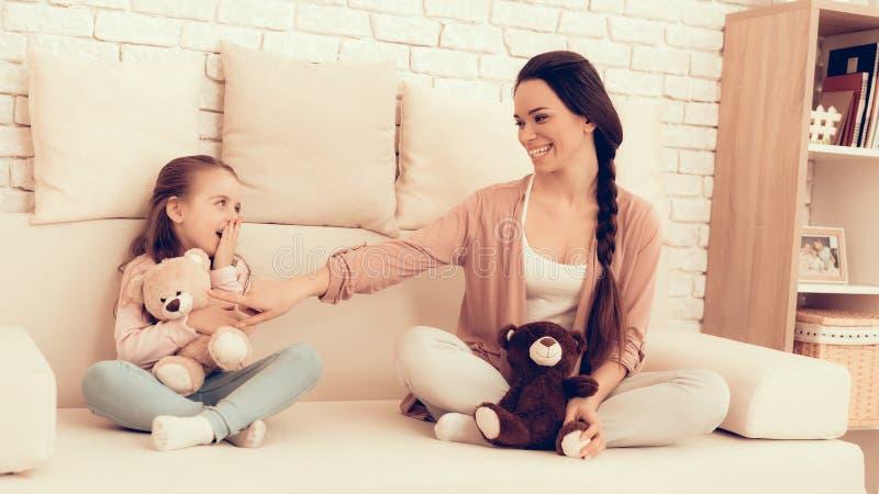 Το Mom και η κόρη με Teddy αντέχουν στα χέρια στο σπίτι στοκ φωτογραφίες