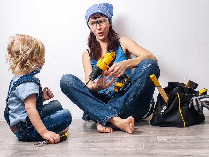 Το Mom και η κόρη στις μπλε φόρμες τζιν κάνουν τις επισκευές και την εργασία με ένα αρσενικό εργαλείο στοκ εικόνες με δικαίωμα ελεύθερης χρήσης
