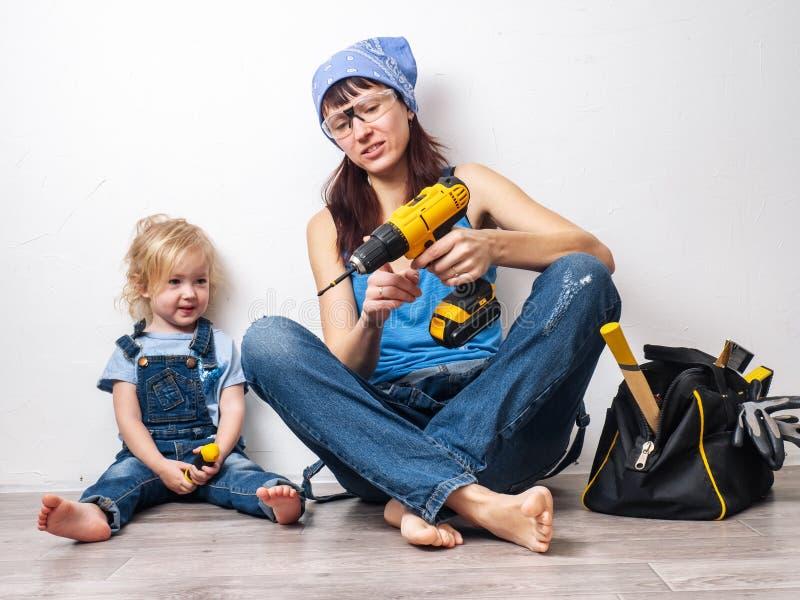 Το Mom και η κόρη στις μπλε φόρμες τζιν κάνουν τις επισκευές και την εργασία με ένα αρσενικό εργαλείο στοκ φωτογραφία