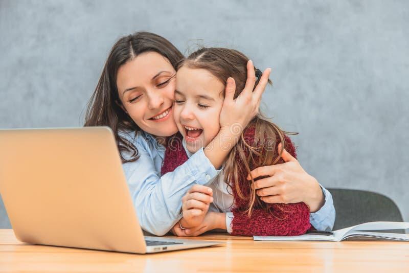 Το Mom και η μαθήτρια κάθονται στον πίνακα Το Mom αγκαλιάζει την κόρη της πάρα πολύ και εξετάζει το lap-top Ειλικρινείς συγκινήσε στοκ φωτογραφία με δικαίωμα ελεύθερης χρήσης