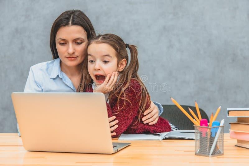 Το Mom και η μαθήτρια κάθονται στον πίνακα Εξέταση ομιλίας το lap-top Το κορίτσι ήταν έκπληκτο να ανοίξει το στόμα της στοκ εικόνες