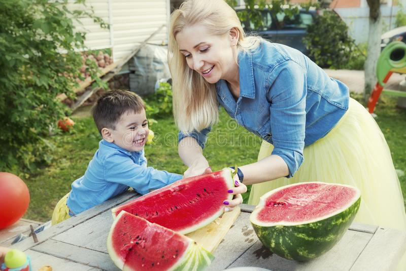 Το Mom και ο γιος κόβουν ένα καρπούζι και ένα γέλιο στον κήπο Αγάπη και τρυφερότητα στοκ εικόνες με δικαίωμα ελεύθερης χρήσης