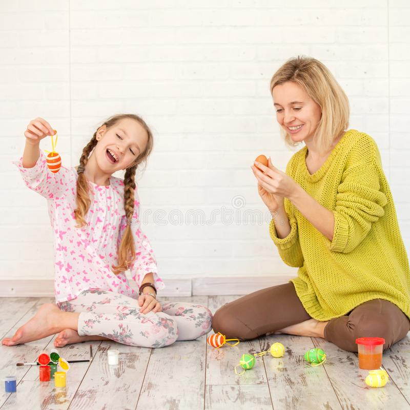 Το Mom και το παιδί διακοσμούν τα αυγά Πάσχας στοκ εικόνες