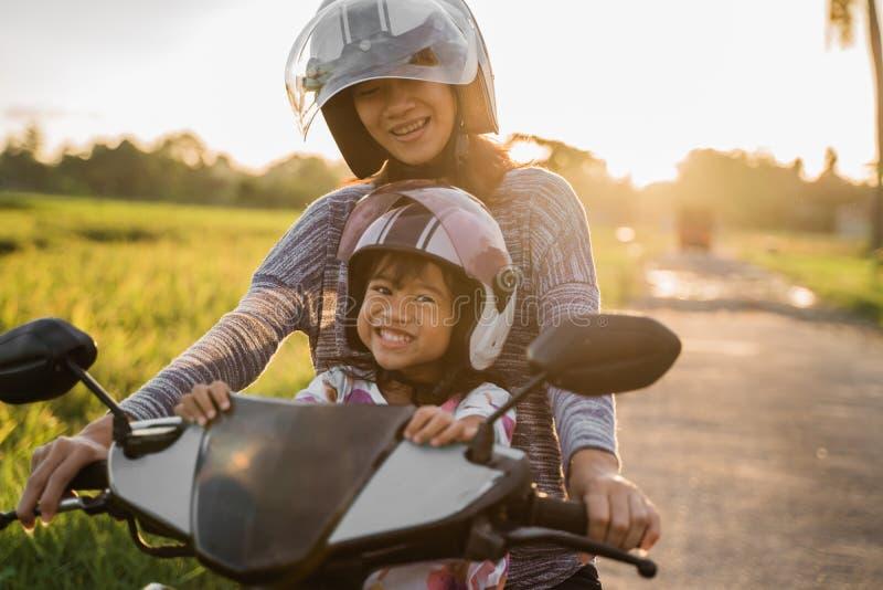 Το Mom και το παιδί της απολαμβάνουν το μηχανικό δίκυκλο μοτοσικλετών στοκ εικόνες