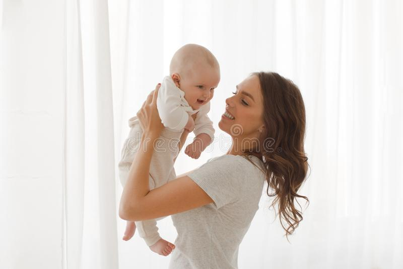 Το Mom κρατά ένα μωρό στο υπόβαθρο παραθύρων όπλων στοκ φωτογραφία