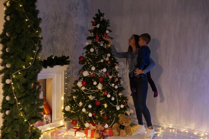 Το Mom με το γιο εξωραΐζει τα νέα δώρα έτους Χριστουγέννων χριστουγεννιάτικων δέντρων στοκ εικόνες με δικαίωμα ελεύθερης χρήσης