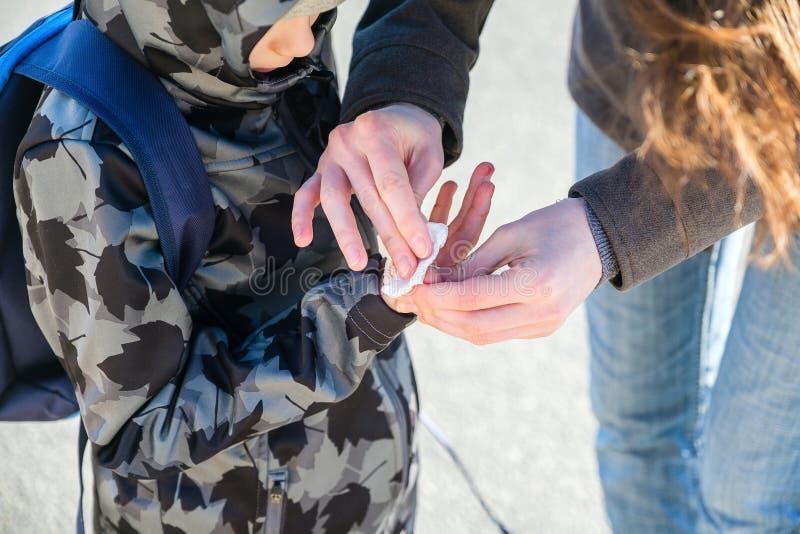 Το Mom σκουπίζει το αίμα από το δάχτυλό του στο αγόρι στοκ εικόνες με δικαίωμα ελεύθερης χρήσης
