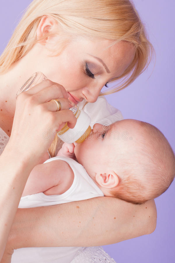 Το Mom ταΐζει το μωρό από το μπουκάλι με τη ρώγα στοκ εικόνα με δικαίωμα ελεύθερης χρήσης