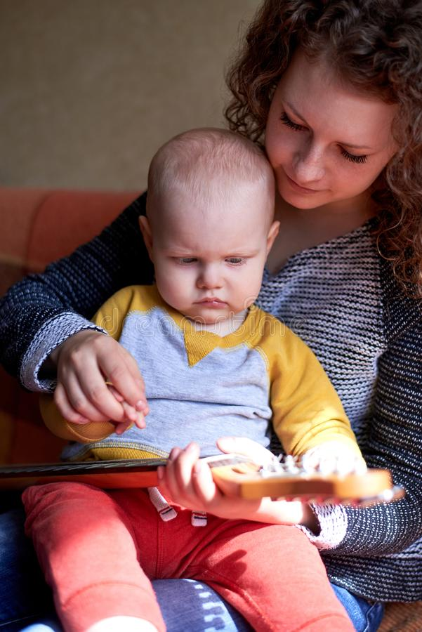 Το Mom της διδάσκει λίγο γιο για να παίξει την κιθάρα Πρόωρη ανάπτυξη παιδιών στοκ εικόνα