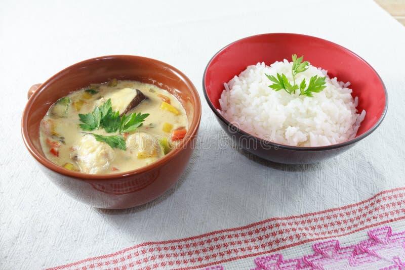 Το Moqueca των πιπεριών ψαριών και κουδουνιών, τρόφιμα Βραζιλιάνος, εξυπηρέτησε με το άσπρο ρύζι, σε έναν ξύλινο πίνακα στοκ φωτογραφία με δικαίωμα ελεύθερης χρήσης