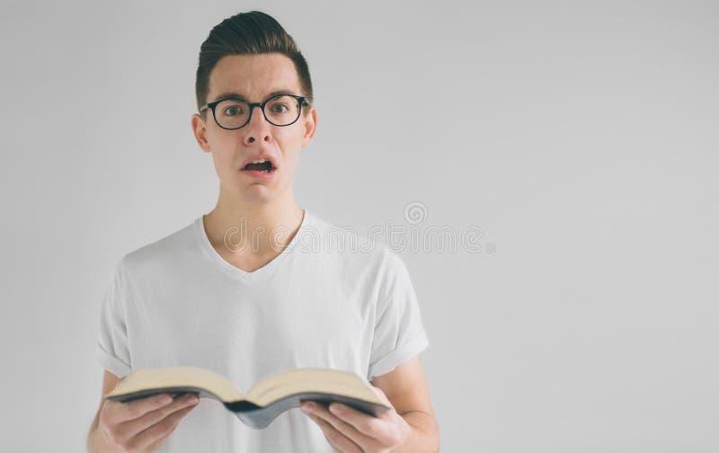 Το Nerd με τα γυαλιά και μια άσπρη μπλούζα διαβάζει ένα βιβλίο σε ένα άσπρο υπόβαθρο στοκ φωτογραφία με δικαίωμα ελεύθερης χρήσης