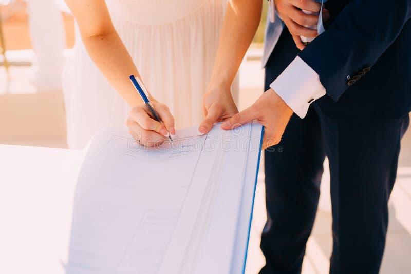 Το Newlyweds έβαλε τις υπογραφές τους στην πράξη της καταχώρησης ενός γάμου στοκ εικόνες