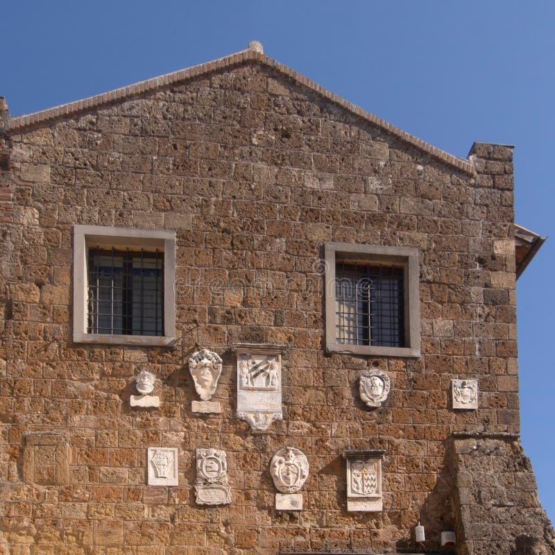 Το Palazzo Pretorio σε Sovana, Grossetto, Ιταλία Με τις αρχαίες bas-ανακουφίσεις στοκ φωτογραφία με δικαίωμα ελεύθερης χρήσης