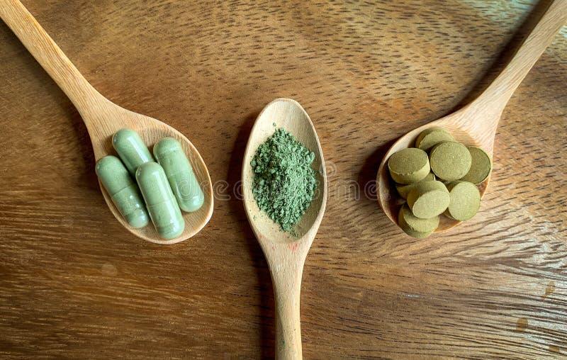 Το paniculata, οι κάψες και η σκόνη Andrographis διαμορφώνουν σε ένα ξύλινο κουτάλι, καφετί ξύλινο πάτωμα στοκ εικόνες με δικαίωμα ελεύθερης χρήσης