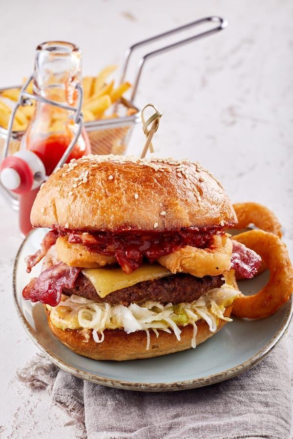 Το Pattie με το κρεμμύδι χτυπά burger με τις τηγανιτές πατάτες στοκ φωτογραφίες