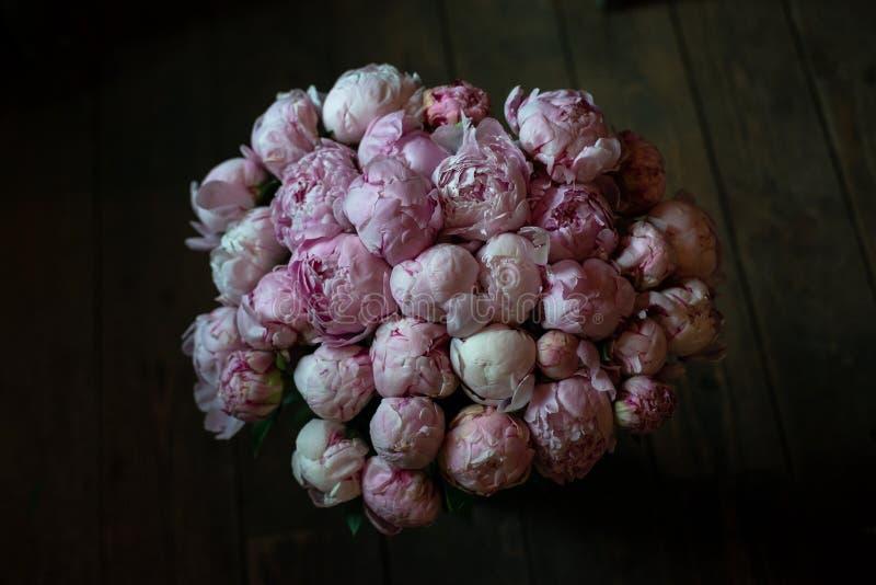 Το Peonies σε μια ανθοδέσμη των λουλουδιών σε ένα πόδι στο εσωτερικό του εστιατορίου για έναν εορτασμό ψωνίζει floristry γαμήλιο  στοκ εικόνες