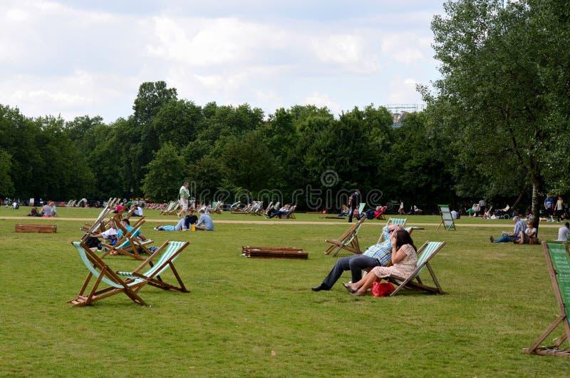 Το Picnickers χαλαρώνει στα deckchairs και τη χλόη Χάιντ Παρκ Λονδίνο Αγγλία στοκ εικόνα με δικαίωμα ελεύθερης χρήσης