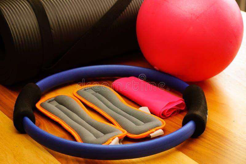 Το Pilates που τίθεται το χαλί με το πόδι ζυγίζει τεντωμάτων τη σφαίρα και στο σπίτι στοκ εικόνες