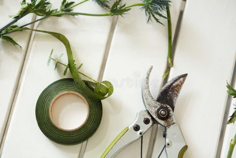 Το Pruner και άλλα εργαλεία ανθοκόμων και τα φρέσκα λουλούδια επάνω στοκ εικόνα