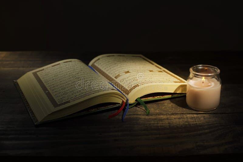 """Το Qur """", το ιερό βιβλίο του Ισλάμ μήνας λατρείας Ramadan, που διαβάζει τα scriptures με τη χρησιμοποίηση ενός φωτός κεριών στοκ εικόνα"""