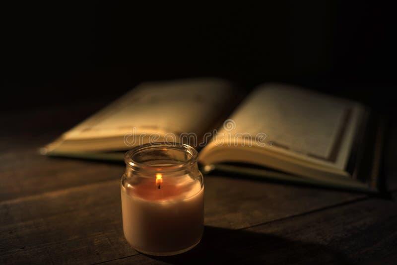 """Το Qur """", το ιερό βιβλίο του Ισλάμ μήνας λατρείας Ramadan, που διαβάζει τα scriptures με τη χρησιμοποίηση ενός φωτός κεριών στοκ εικόνες"""