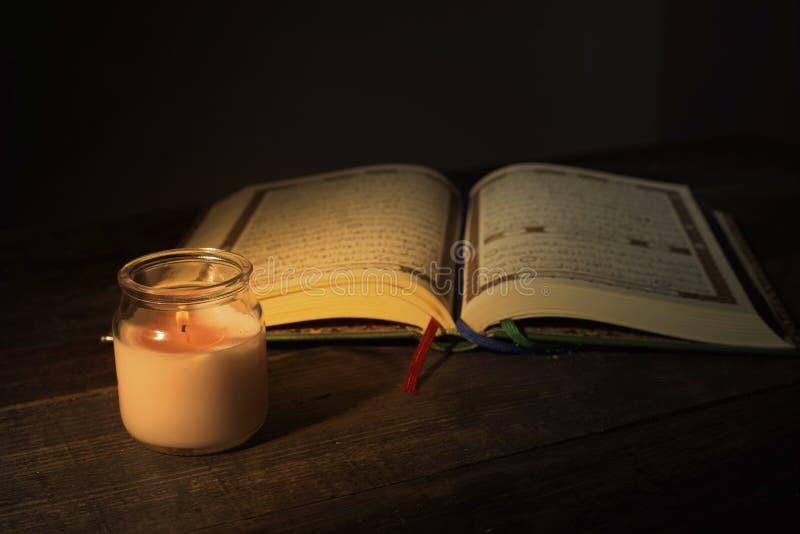 """Το Qur """", το ιερό βιβλίο του Ισλάμ μήνας λατρείας Ramadan, που διαβάζει τα scriptures με τη χρησιμοποίηση ενός φωτός κεριών στοκ εικόνα με δικαίωμα ελεύθερης χρήσης"""