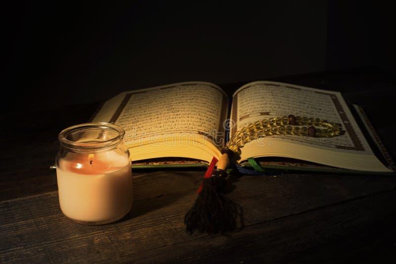 """Το Qur """", το ιερό βιβλίο του Ισλάμ μήνας λατρείας Ramadan, που διαβάζει τα scriptures με τη χρησιμοποίηση ενός φωτός κεριών στοκ φωτογραφία με δικαίωμα ελεύθερης χρήσης"""