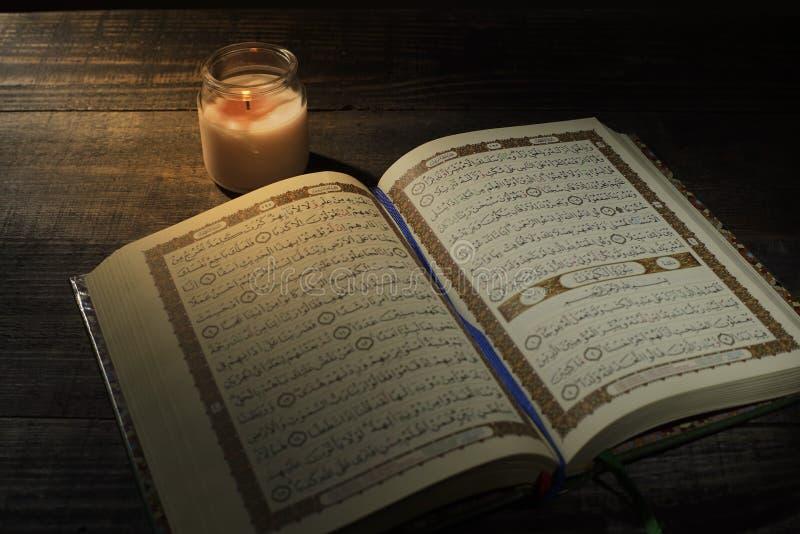 """Το Qur """", το ιερό βιβλίο του Ισλάμ μήνας λατρείας Ramadan, που διαβάζει τα scriptures με τη χρησιμοποίηση ενός φωτός κεριών στοκ φωτογραφία"""