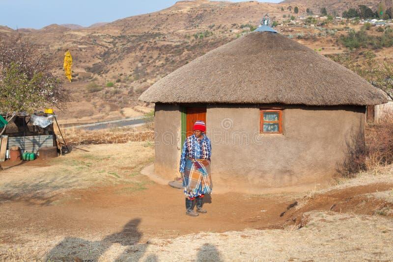 Το Ramabanta, ενήλικη αφρικανική γυναίκα του Λεσόθο στα παραδοσιακά γενικά ενδύματα στέκεται στο σπίτι στο χωριό, ηλικιωμένη γυνα στοκ εικόνες