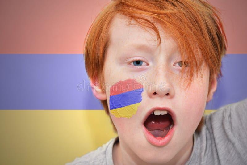 Το Redhead αγόρι ανεμιστήρων με την αρμενική σημαία χρωμάτισε στο πρόσωπό του στοκ εικόνα