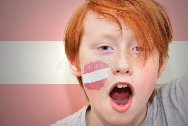Το Redhead αγόρι ανεμιστήρων με την αυστριακή σημαία χρωμάτισε στο πρόσωπό του στοκ εικόνες