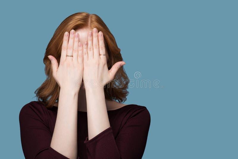 Το Redhead κορίτσι Burgundy στο σακάκι καλύπτει το πρόσωπό του με δύο χέρια σε ένα μπλε υπόβαθρο στοκ φωτογραφία με δικαίωμα ελεύθερης χρήσης