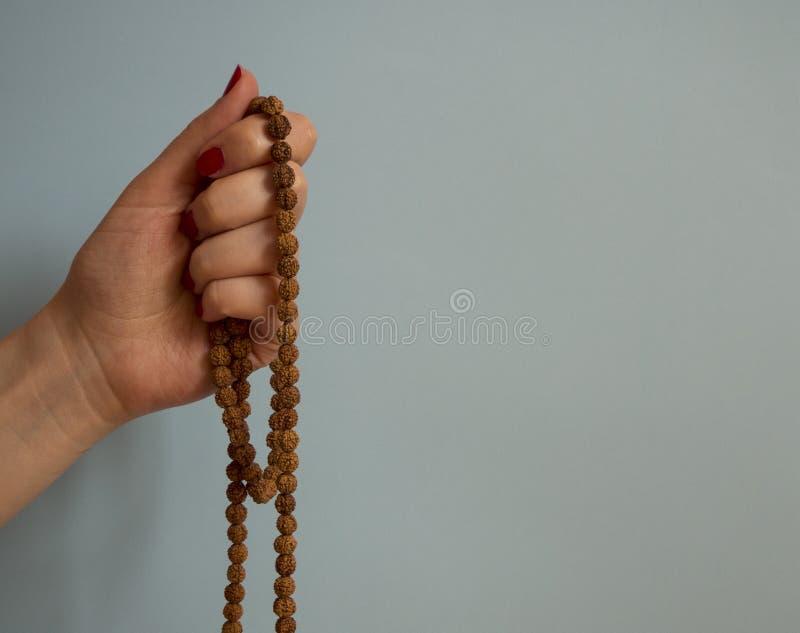 Το rudraksha εκμετάλλευσης μιας γυναίκας hande διακοσμεί rosary στο μπλε υπόβαθρο με το διάστημα αντιγράφων με χάντρες στοκ φωτογραφία με δικαίωμα ελεύθερης χρήσης